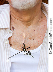 Time passing - Clock hands placed on an elderly man's chest.