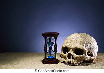 Time Passing - Death concept. One human skull near hourglass...
