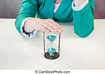 time passing - hand over green sandglass concept