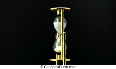 Time passing while sand falls through hourglass. Black background