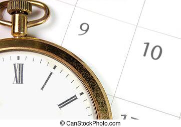 Pocket watch on top of a calendar