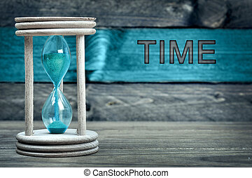 Time text and hourglass on table
