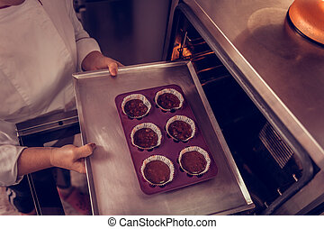Top view of muffins being put in the oven