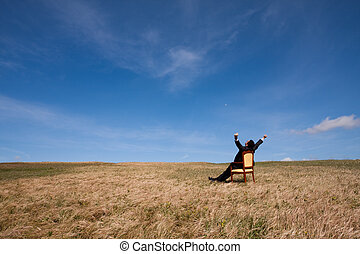 Time to be free - businessman at the field relaxing and...