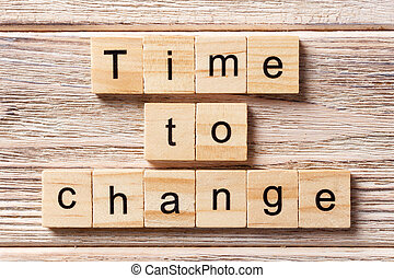 TIME TO CHANGE word written on wood block. TIME TO CHANGE text on table, concept
