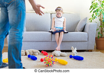 time to clean up your toys! Little girl playing with tablet pc, ignoring her father.