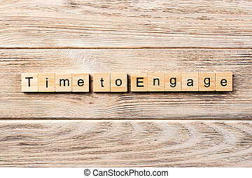 Time to engage word written on wood block. Time to engage text on table, concept