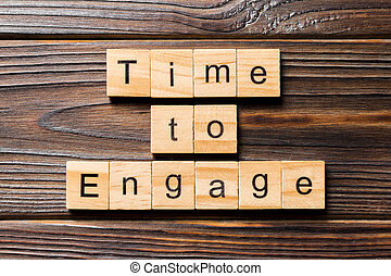Time to engage word written on wood block. Time to engage text on wooden table for your desing, Top view concept