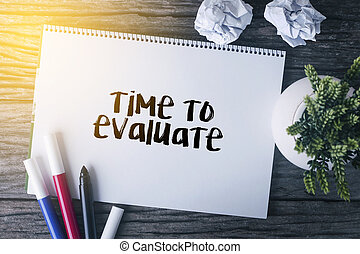 Time to evaluate word with Notepad and green plant on wooden background.