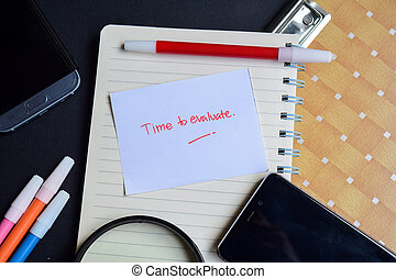 Time to Evaluate written on paper isolated on black table
