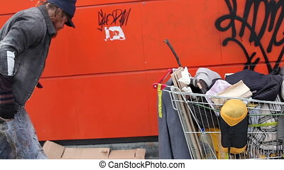 Time to go - Homeless guy collecting his possessions and...