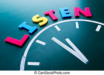 Time to listen concept, color word and clock on blackboard