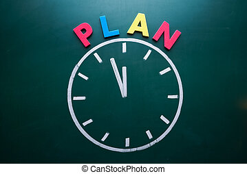 Time to plan concept, color word and clock on blackboard