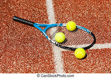 Time to play. Close-up of tennis racket and three tennis balls laying on the court