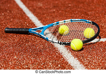 Time to play tennis. Close-up of tennis racket and three tennis balls laying on the court