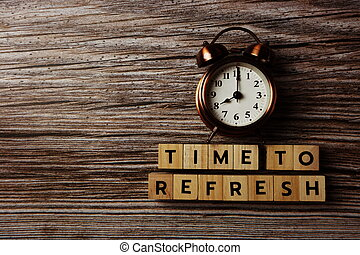 Time To Refresh alphabet letter with alarm clock on wooden background