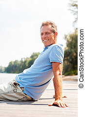 Time to relax. Side view of happy mature man looking away and smiling while sitting at the quayside