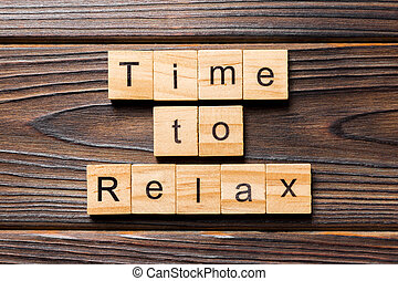 time to relax word written on wood block. time to relax text on table, concept