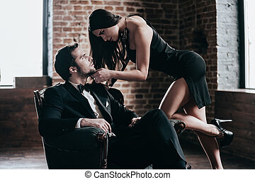 Time to seduce. Beautiful young woman in cocktail dress leaning to her boyfriend sitting in chair while looking at each other in loft interior