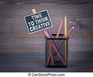 Time to think creative. A small blackboard chalk and colored pencil on wood background