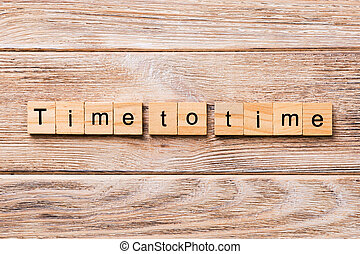 Time to time word written on wood block on wooden table for your desing, concept