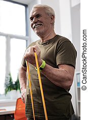 Delighted cheerful man standing in the exercise room