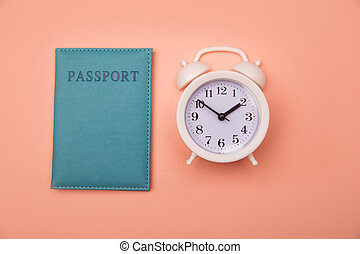 Time to travel. Passport and clock on pink background. Top view