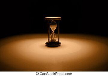 Time - Vintage hourglass on sephia tones .