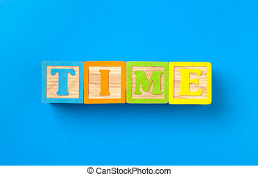 Time. Wooden colorful alphabet blocks on blue background, flat lay, top view.