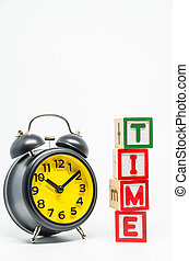 TIME word wooden block arrange in vertical style with black retro alarm clock on white background and selective focus