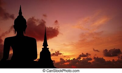 Timelapse abstract of a silhouetted Buddha image against a sunset sky with puffy clouds billowing and drifting in the background.