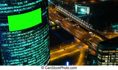 Timelapse - blank green screen billboard on building and cars traffic at night