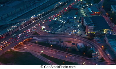 Timelapse: fast moving cars traffic and warm street light at night, gets dark