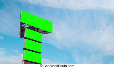 Timelapse: four blank green billboards or large displays and moving white clouds against blue sky. Consumerism, time lapse, advertising, green screen, template, mock up, copy space, chroma key concept