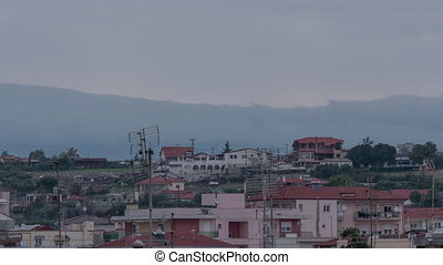 Timelapse in Nea Kallikratia, Greece at sunset seen roofs of houses with antennas and mount Olympus