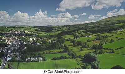 Timelapse Ireland cityscape aerial view: white houses, roads, ways. Irish nature landscape meadows, fields in coast Ballycastle port town, Antrim County. Footage shot in 2K, QHD