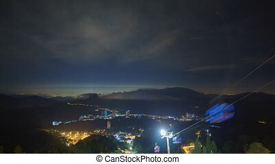 Timelapse light trails of moving cable cars overlooking scenic mountain view at Genting Highland.