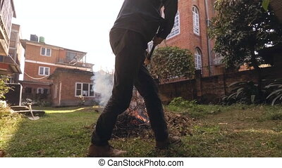 Timelapse of a man making a fire in garden