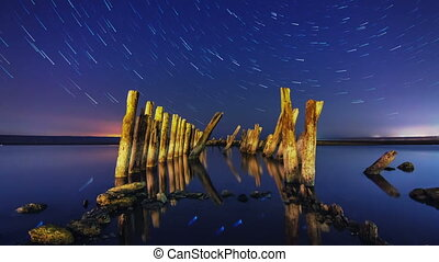 Timelapse of a star trails at night with wooden columns and firth water in the foreground