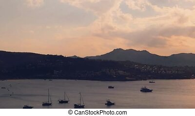 Timelapse of a sunset sky over the sea and mountain ...