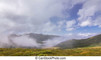 Timelapse of beautiful summer landscape in mountains with clouds passing by against blue sky