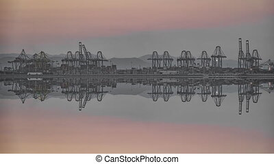 Timelapse of blurred port cranes reflection at dusk
