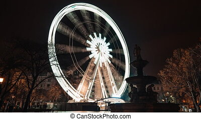 Timelapse of brightly lit ferris wheel ride, which spinning ...