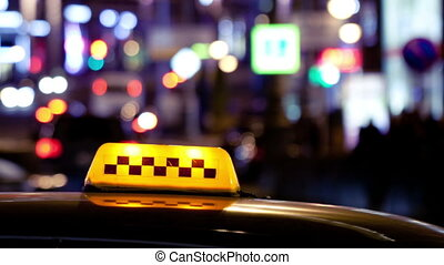 Timelapse of city traffic at night behind taxi sign