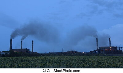 Timelapse of clouds of smoke billowing from smokestacks into...