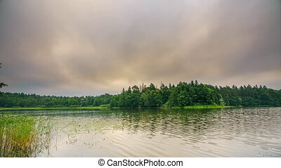 Timelapse of cloudy morning on a forest lake - Timelapse of...