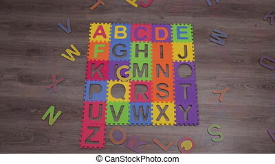 Timelapse shot of collecting the mat puzzle with colorful English alphabet. Funny learning