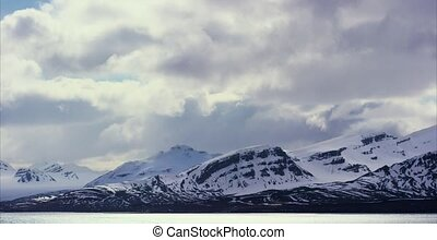Timelapse of dramatic clouds over mountains in the arctic -...
