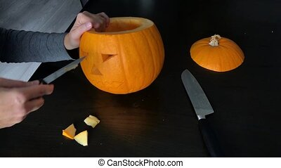 Timelapse of female hands carving a Halloween pumpkin -...