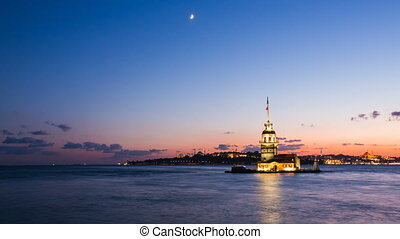 Timelapse of Maiden Tower or Kiz Kulesi with floating tourist boats on Bosphorus in Istanbul at night